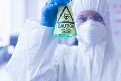 Científico en traje protector con la sustancia química peligrosa en frasco fotografía de archivo libre de regalías