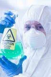 Científico en traje protector con la sustancia química peligrosa en frasco imagenes de archivo