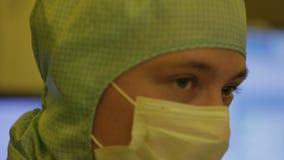 Científico en trajes estéril, máscara del ingeniero esté en una zona limpia que mira un proceso avanzó tecnológico la fábrica almacen de video