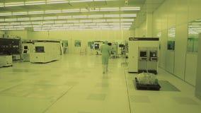Científico en trajes estéril, máscara del ingeniero del plan general esté en la zona limpia, toma los productos del microchip Alt almacen de video