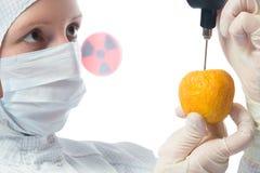 científico en un traje protector blanco, controles la manzana para la presencia de radiación, en blanco fotografía de archivo