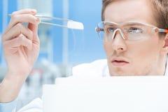 Científico en vidrios protectores y guantes que miran la muestra química Imagen de archivo