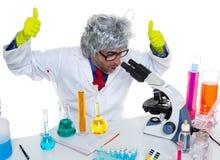 Científico enojado loco del empollón en el microscopio del laboratorio Imágenes de archivo libres de regalías