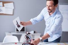 Científico feliz que lleva a cabo un prototipo de su invención imagen de archivo