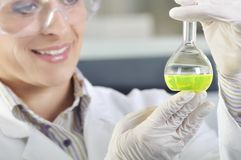 Científico joven atractivo del estudiante del doctorado observando el cambio del color después del destillation de la solución en fotos de archivo libres de regalías