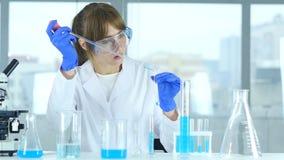 Científico joven de sexo femenino que hace la reacción en laboratorio metrajes
