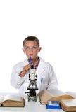 Científico joven que pone su pluma a su barbilla fotografía de archivo