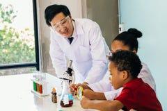 Científico joven que sostiene un frasco y que enseña a dos niños mezclados afroamericanos en el experimento de la química imagenes de archivo