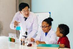 Científico joven que sostiene un frasco y que enseña a dos niños mezclados afroamericanos en laboratorio de química foto de archivo libre de regalías