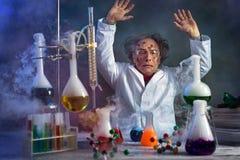 Científico loco en el laboratorio rodeado por el humo de la explosión imagenes de archivo