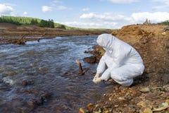 Científico o biólogo que lleva los uniformes protectores que trabajan junto en análisis de agua foto de archivo libre de regalías