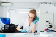 Científico que analiza la diapositiva del microscopio en el laboratorio Trabajo femenino en laboratorio con el microscopio Examen Fotos de archivo libres de regalías