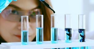 Científico que cae el líquido negro en los tubos de ensayo metrajes