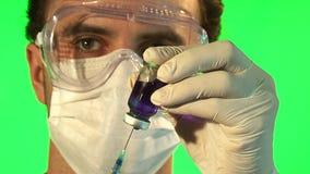 Científico que inyecta el líquido azul en la botella almacen de video