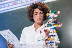 Científico que mira la DNA en laboratorio imagen de archivo