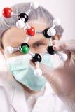 Científico que mira sobre los átomos Fotografía de archivo libre de regalías
