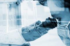 Científico que mira a través de un microscopio para las muestras de la prueba de la química Imagen de archivo libre de regalías