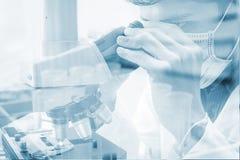 Científico que mira a través de un microscopio para las muestras de la prueba de la química Fotografía de archivo libre de regalías