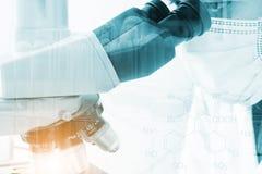 Científico que mira a través de un microscopio para las muestras de la prueba de la química Fotografía de archivo
