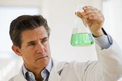 Científico que soporta el tarro de productos químicos Imagen de archivo libre de regalías