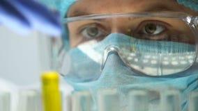Científico que toma el tubo de ensayo con el líquido amarillo, extracto de la perfumería, producción metrajes