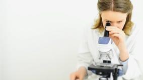 Científico que usa el microscopio en laboratorio almacen de metraje de vídeo