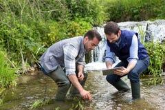 Científico y biólogo que trabajan junto en análisis de agua imagenes de archivo