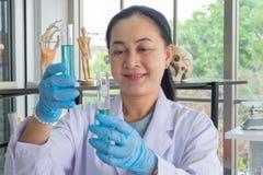 Científicos asiáticos de la Edad Media de la mujer en laboratorio r fotos de archivo