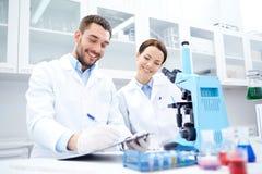 Científicos con el tablero y el microscopio en laboratorio Imagen de archivo