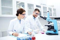 Científicos con el tablero y el microscopio en laboratorio Fotos de archivo
