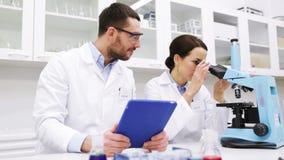 Científicos con PC y el microscopio de la tableta en laboratorio almacen de video