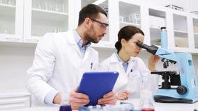 Científicos con PC y el microscopio de la tableta en laboratorio metrajes