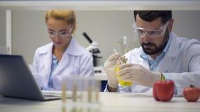 Científicos de sexo masculino que consultan con el colega mientras que la inyección sazona con pimienta con las sustancias químic almacen de video