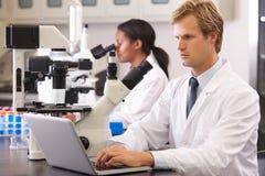 Científicos de sexo masculino y de sexo femenino que usan los microscopios en laboratorio Foto de archivo