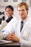 Científicos de sexo masculino y de sexo femenino que usan los microscopios en laboratorio Fotografía de archivo