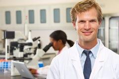 Científicos de sexo masculino y de sexo femenino que usan los microscopios en laboratorio Fotografía de archivo libre de regalías