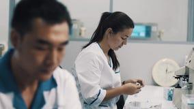 Científicos en los trajes blancos en el laboratorio multicultural que trabaja con las lentes almacen de video
