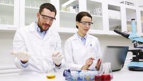Científicos jovenes que hacen la prueba o la investigación en laboratorio metrajes