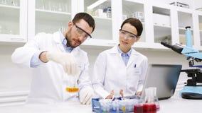 Científicos jovenes que hacen la prueba o la investigación en laboratorio almacen de video