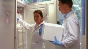 Científicos que usan el refrigerador grande en laboratorio almacen de video