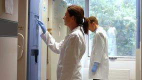 Científicos que usan el refrigerador grande en laboratorio metrajes