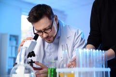 Cient?fico de sexo masculino que usa el microscopio en laboratorio de qu?mica imágenes de archivo libres de regalías