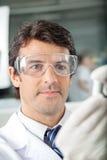 Científico In Protective Eyewear en el laboratorio Imagenes de archivo