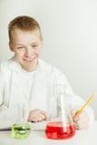 Científico sonriente del muchacho con el cuaderno y los cubiletes Fotos de archivo libres de regalías