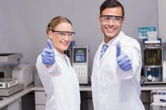 Científicos sonrientes que miran los pulgares de la cámara para arriba Fotos de archivo libres de regalías