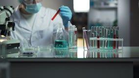 Cientista do laboratório que procura o tubo de ensaio necessário com sangue para examinar vídeos de arquivo