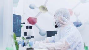 Cientista em um laboratório moderno que trabalha no computador filme