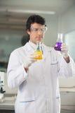 Cientista Examining Flasks With diferente imagens de stock