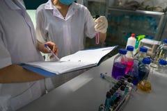 Cientista fêmea asiático que escreve para baixo notas e relatório de teste da pesquisa com os tubos de ensaio no laboratório, clo Fotos de Stock