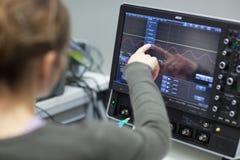 Cientista fêmea em um laboratório do sistema ótico do quantum (cor t Fotos de Stock Royalty Free